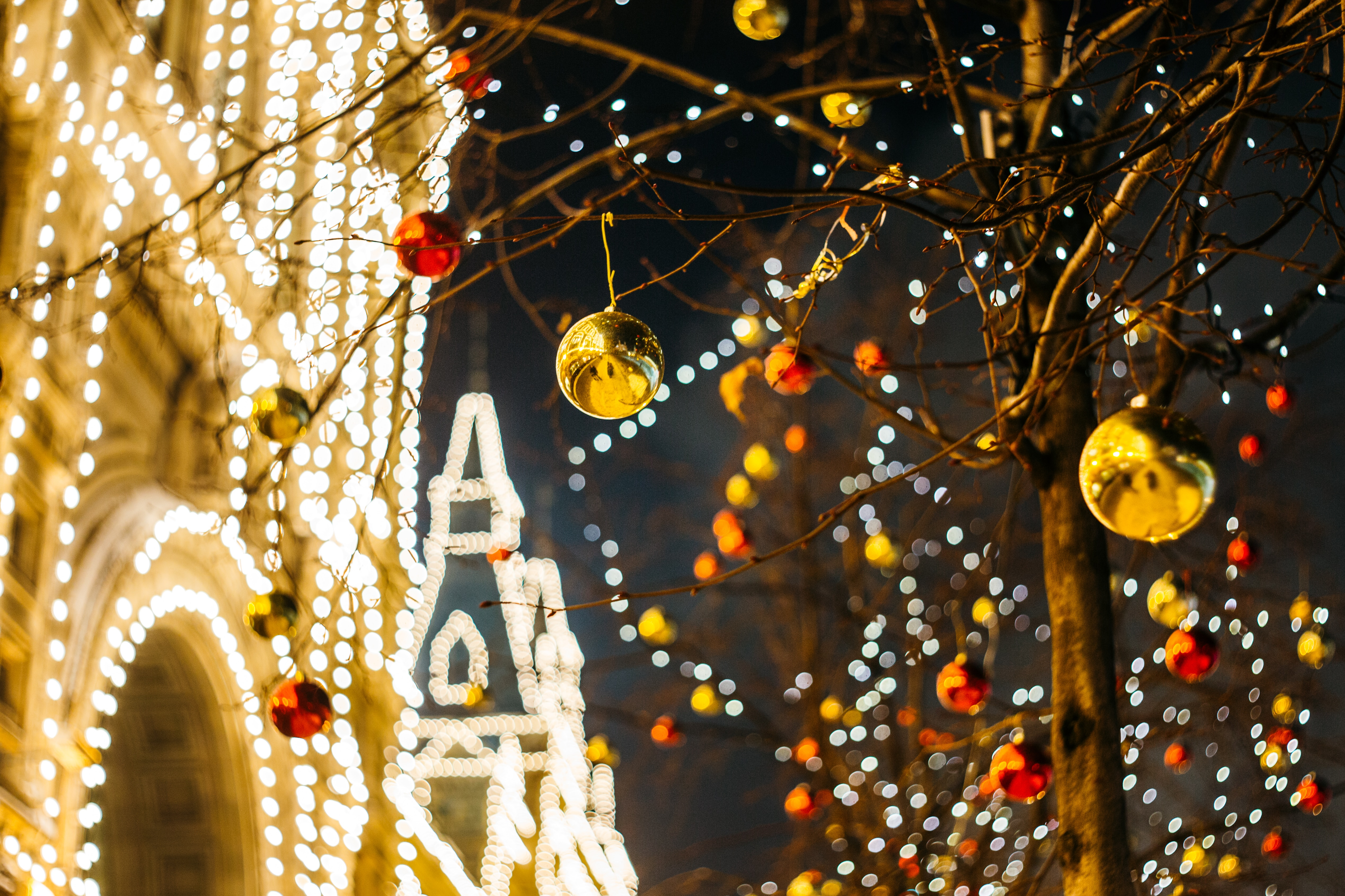 A tree decorated with ornaments in front of a holiday light display.