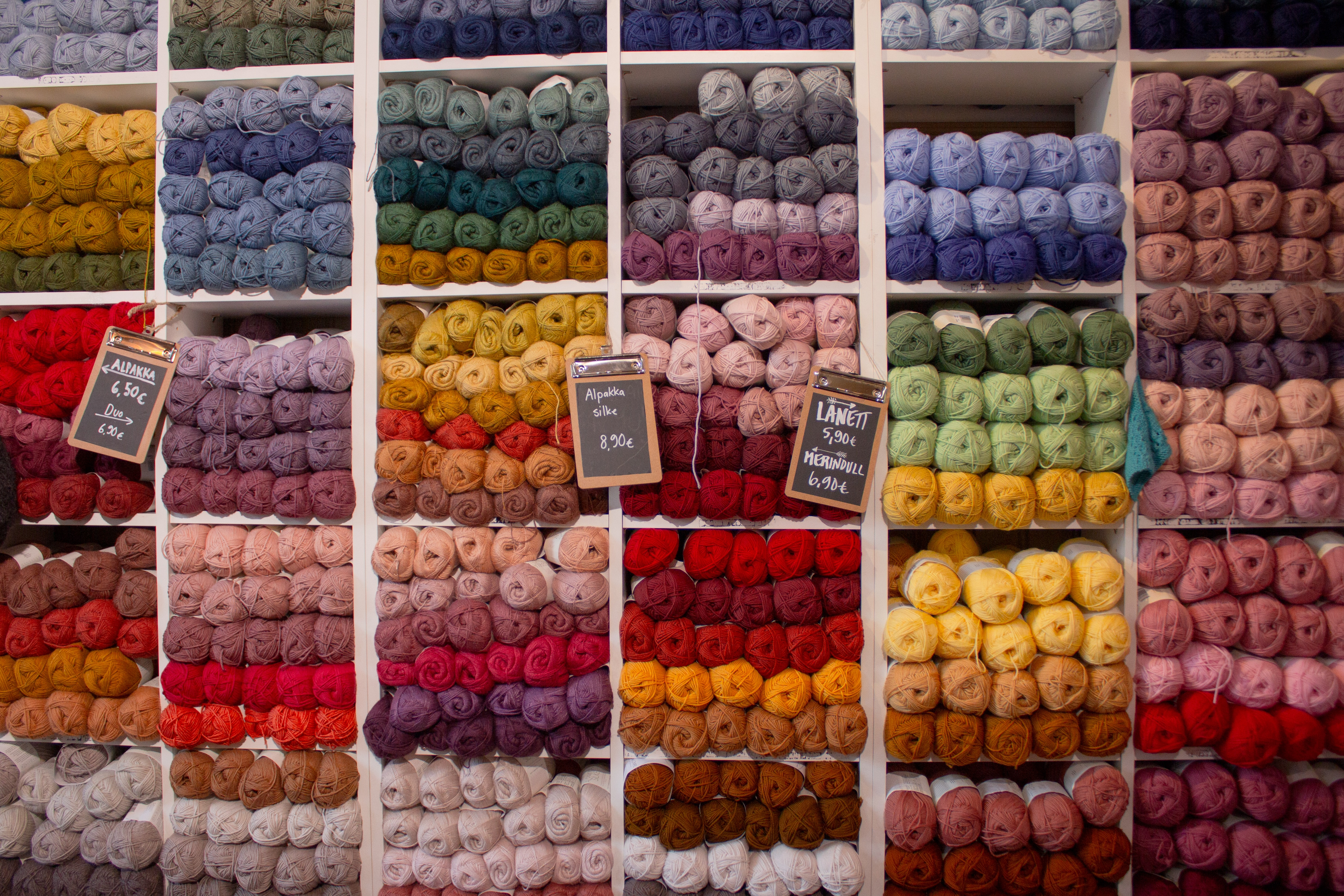 A wall of shelves stocked with yarn in a variety of colors.