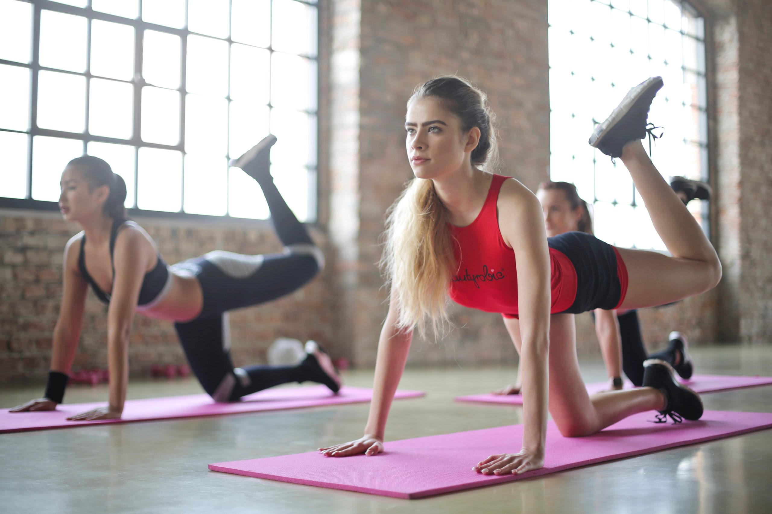 Three women stretching on yoga mats in a pilates class.