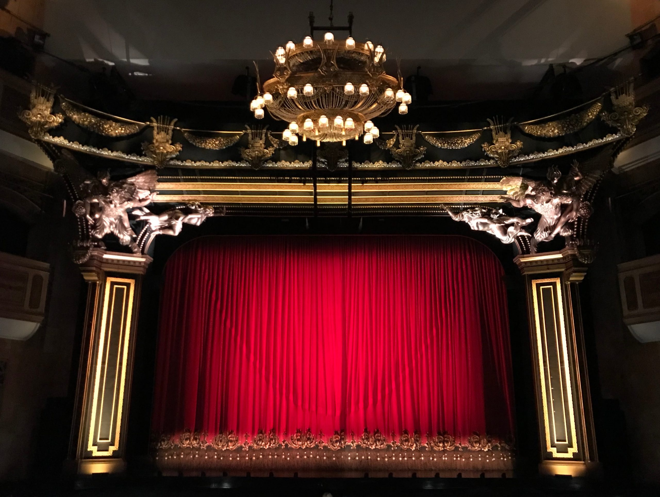 A theater stage with the curtain closed.