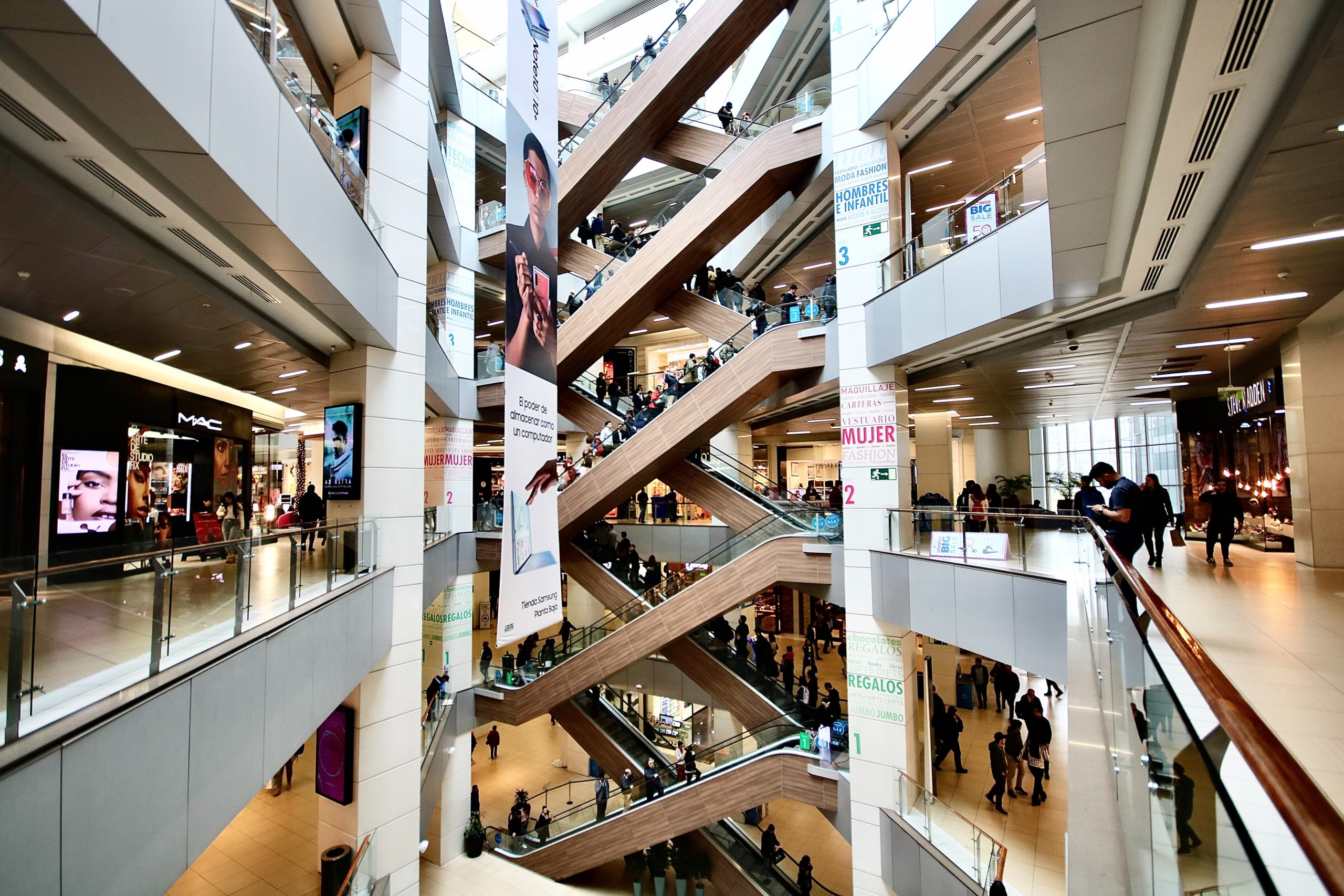 A wide view of a shopping mall's escalators and stores on several floors.