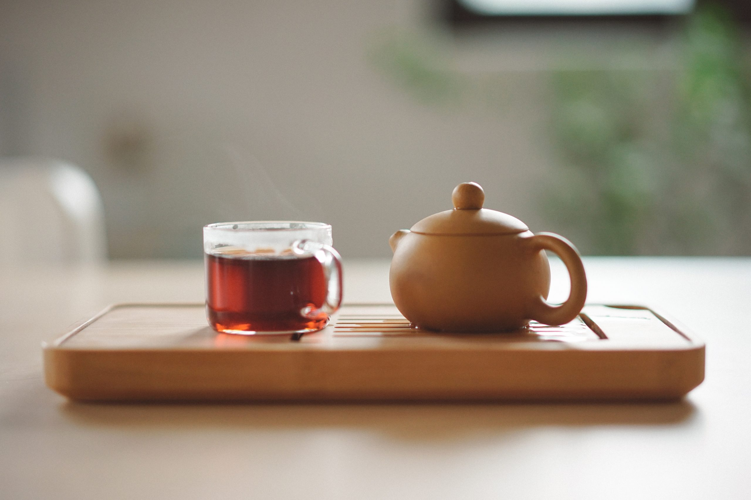 A mug of tea and a tea pot on a serving tray.