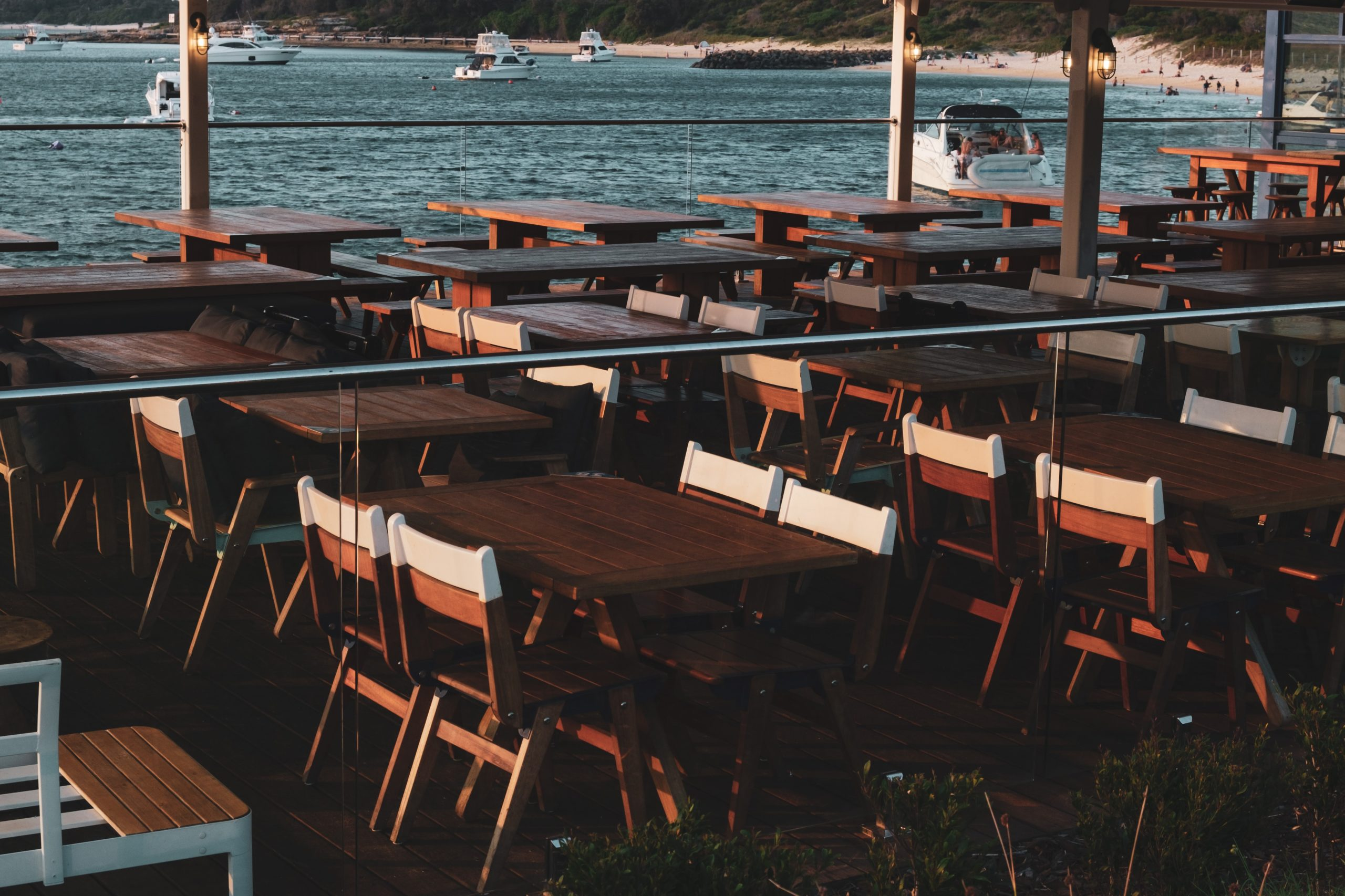 Dining tables along a waterfront.
