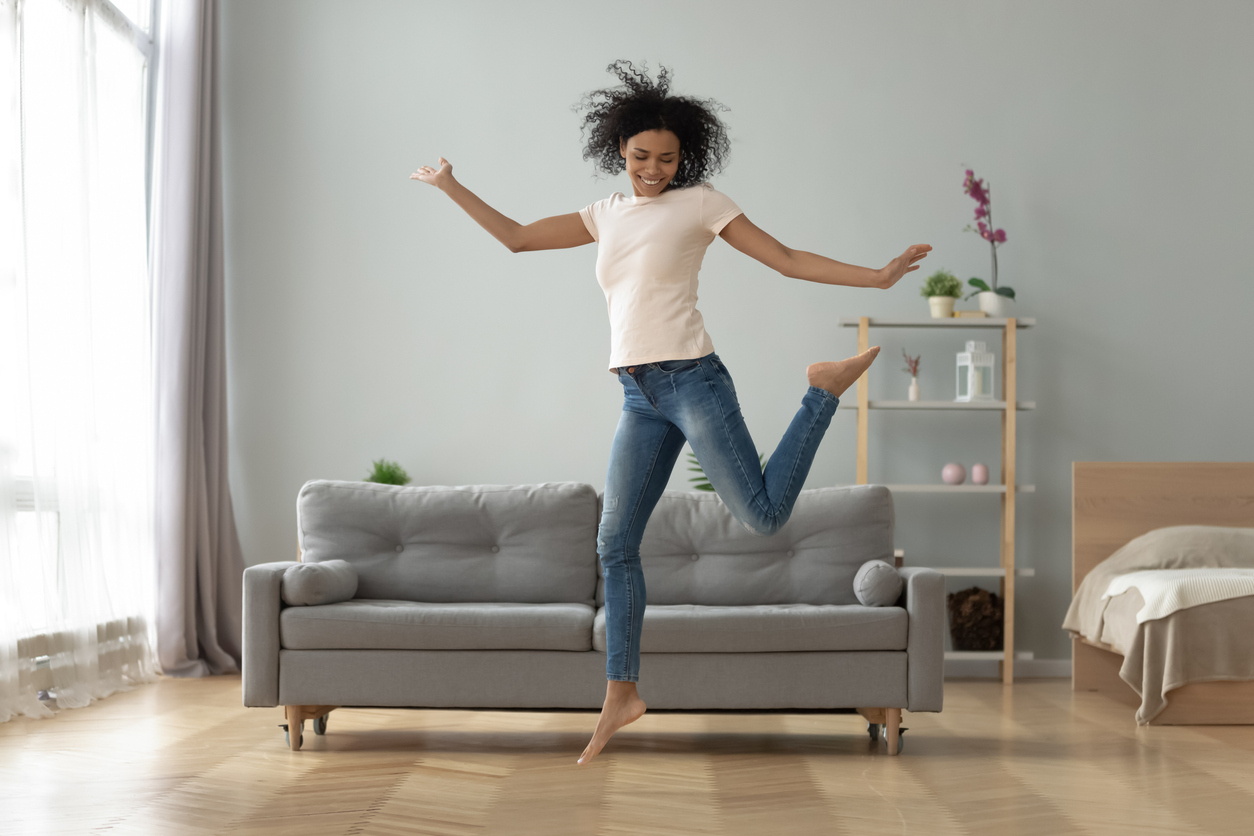 A woman dancing inside her apartment.