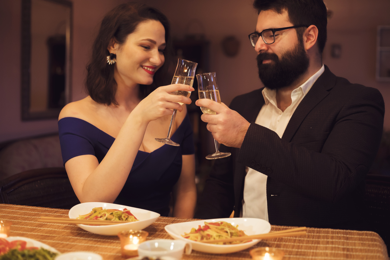 couple toasts with white wine enjoying chinese food date at home