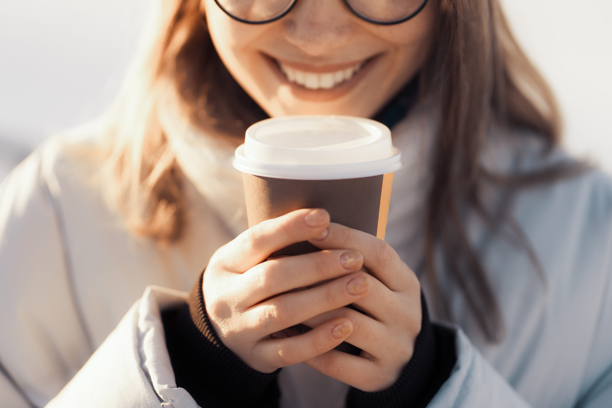 Happy young woman holding a takeaway coffee cup