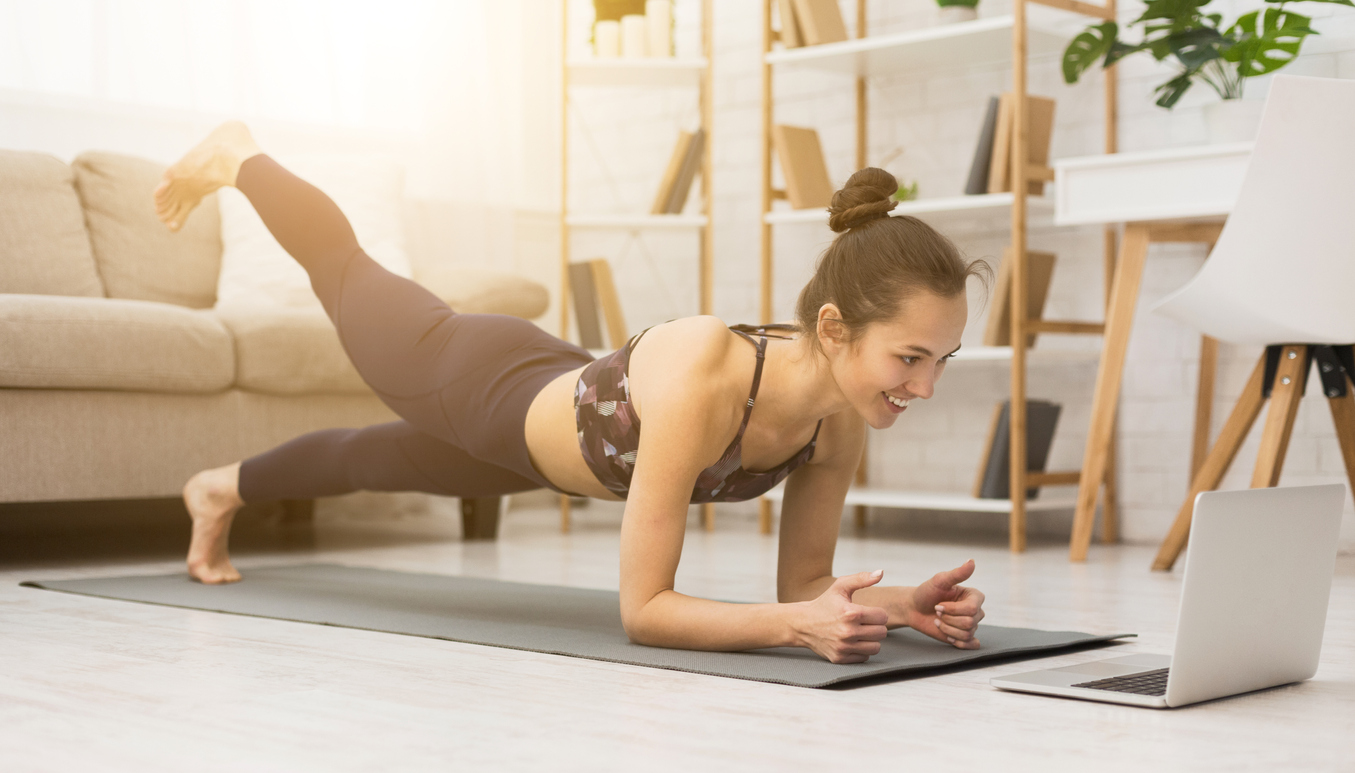 young woman taking virtual yoga class at home