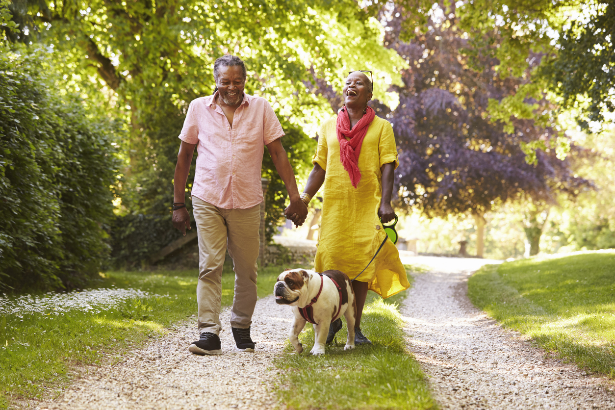 older couple walking with pet bulldog on walking trail