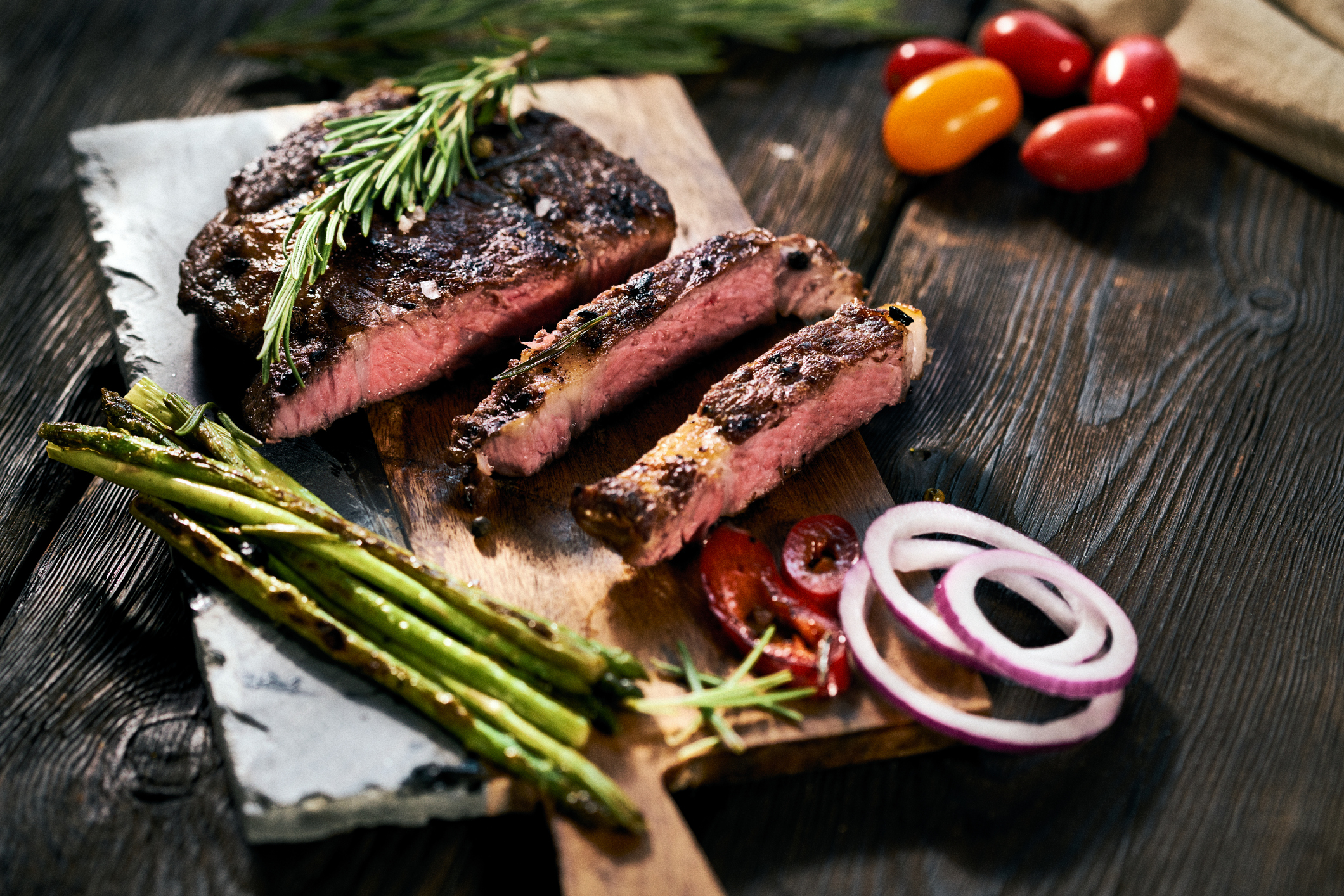sliced steak on a cutting board with vegetables