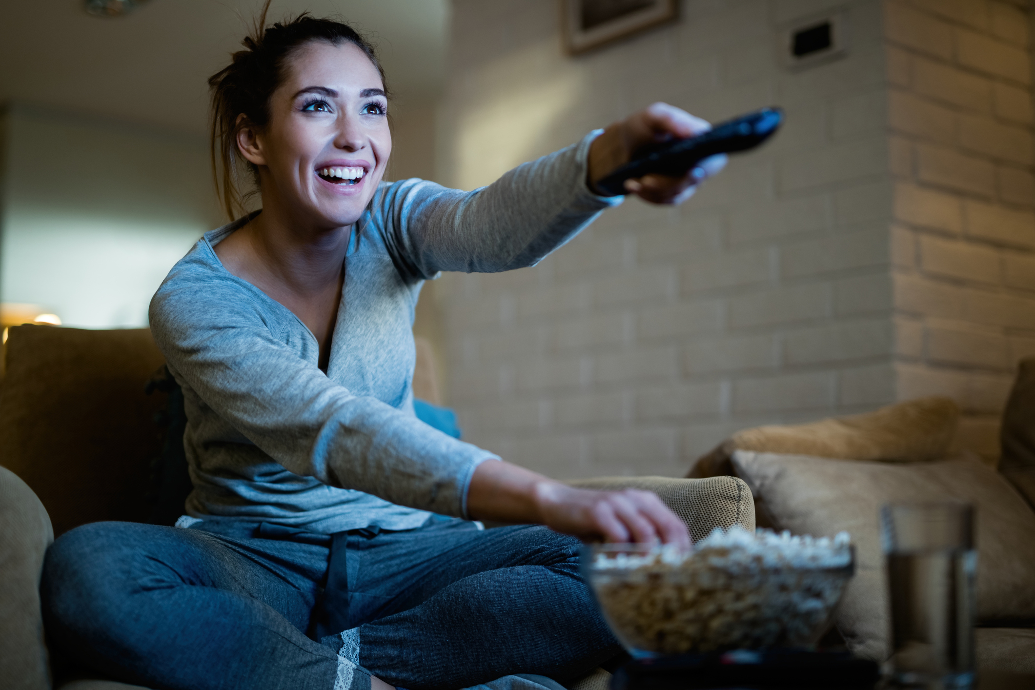 A woman pointing the remote at the TV while reaching for popcorn.