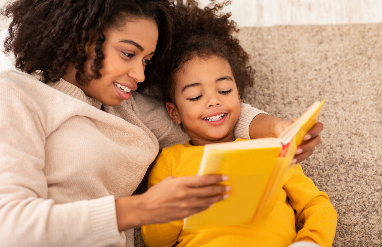 A woman reading a book to her daughter while sitting on a couch.