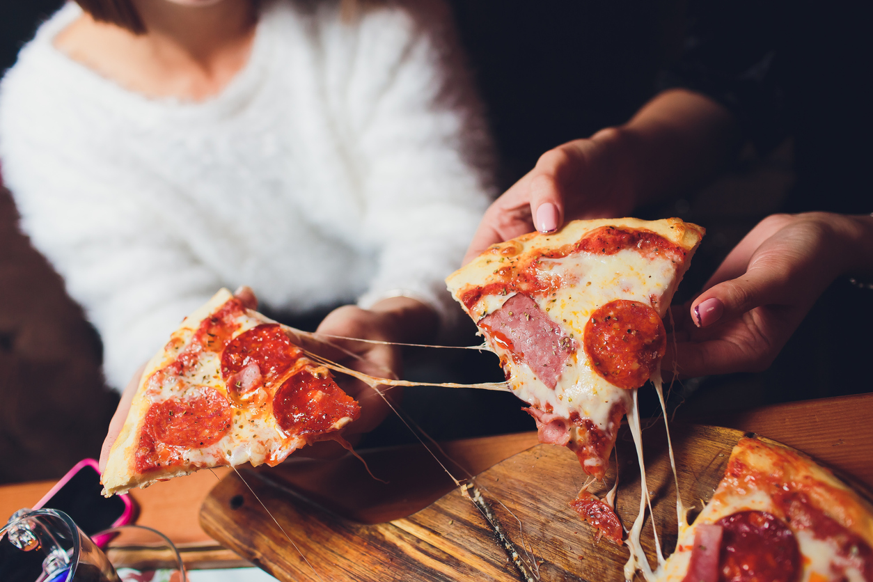 Two people picking up slices of pepperoni pizza.