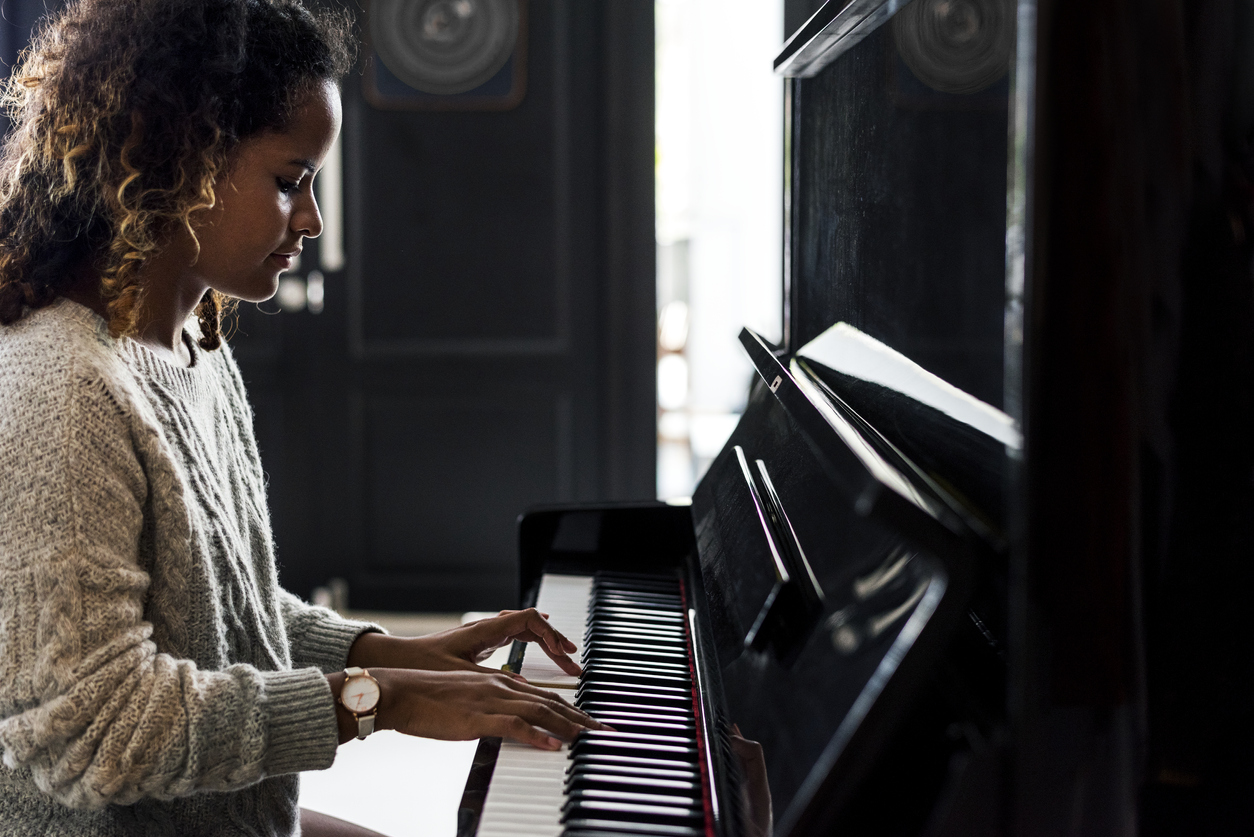 Woman playing the piano in her apartment