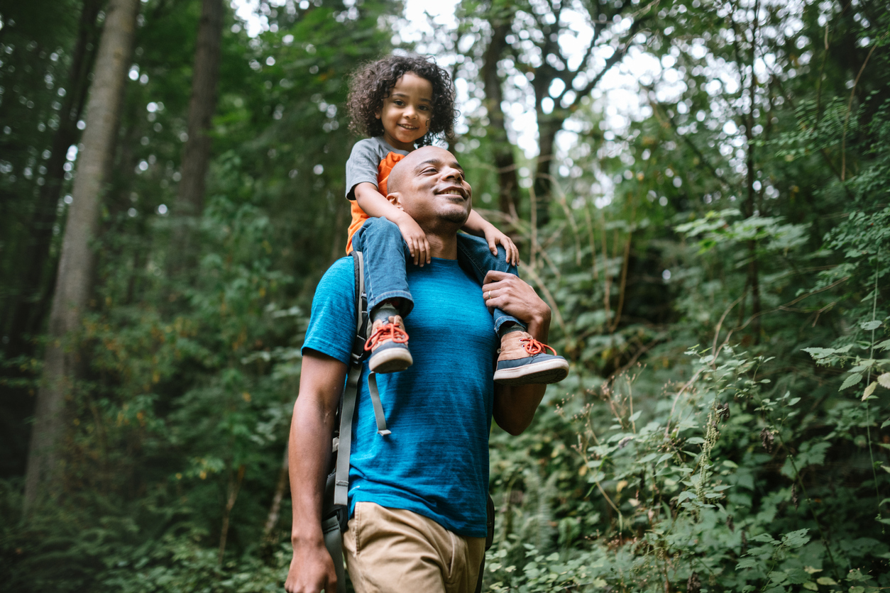 A man with a child on his shoulders walking through a nature park in Germantown