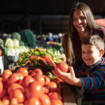 Mother and son picking out fresh produce from Germantown farmer's markets.