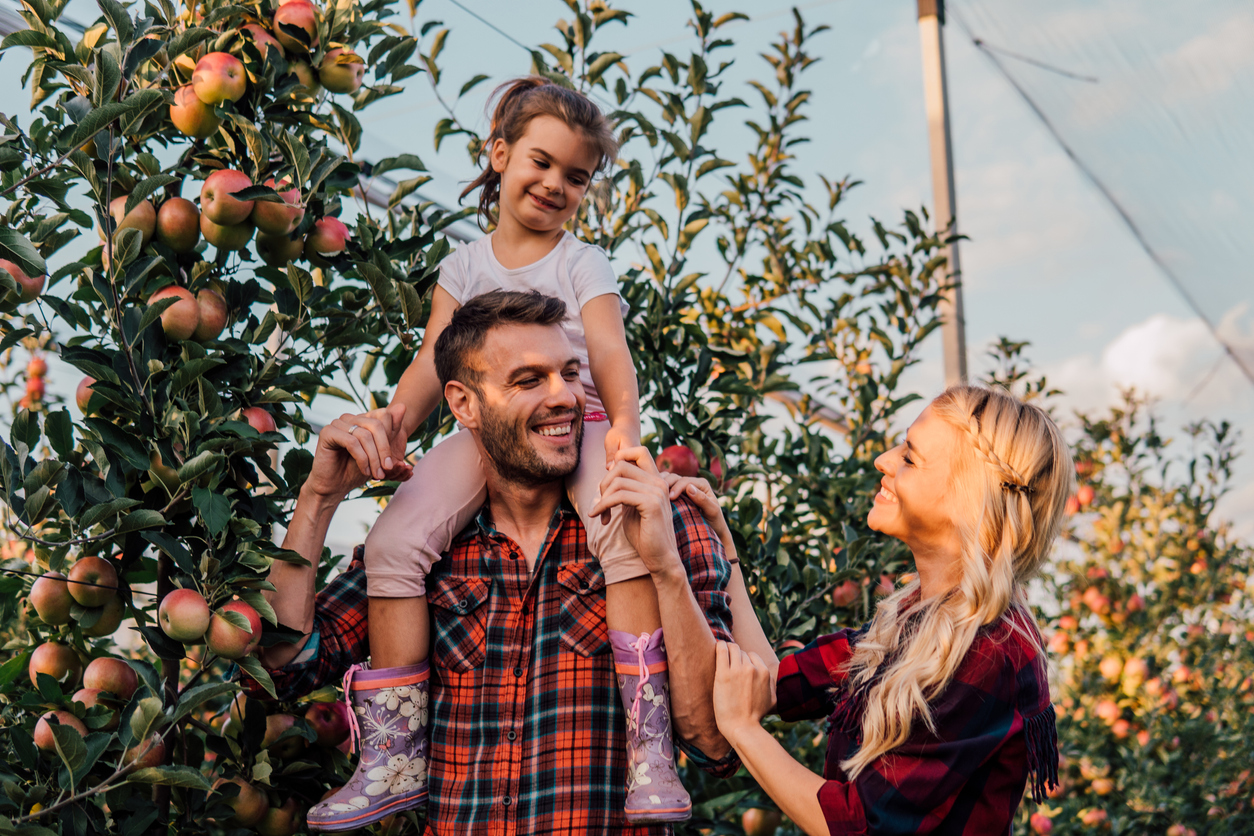 Happy family celebrating the fall season at one of the orchards near Germantown.